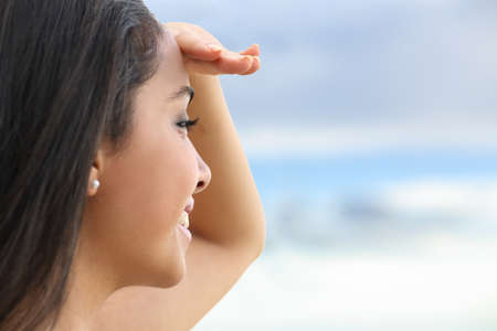 Close up of a beautiful woman looking at the horizon with a hand in forehead with the sky