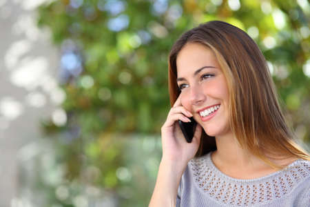 Beautiful and elegant woman on the mobile phone with a green unfocused background             photo