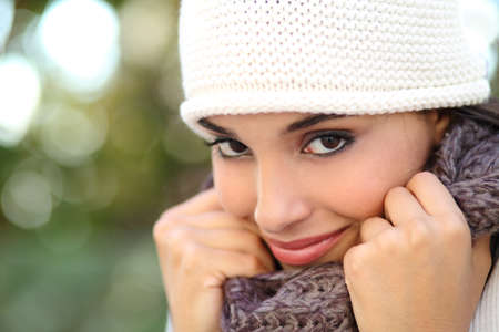 warmly: Beautiful arab woman portrait warmly clothed with an unfocused green background