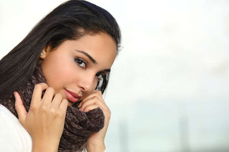 clothed: Portrait of a beautiful arab woman face warmly clothed and grabbing a scarf outdoor     Stock Photo