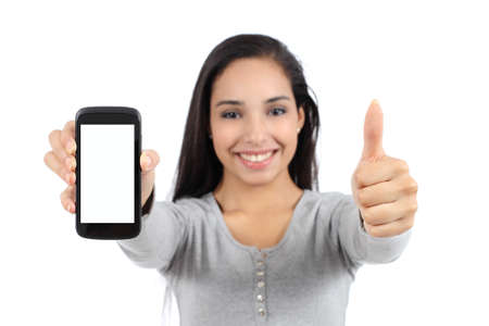 Pretty smiling woman showing a blank vertical smart phone screen and thumb up isolated on a white background