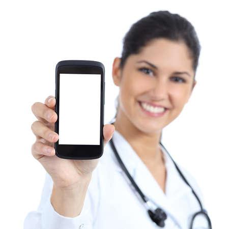 smart: Mooie vrouwelijke arts glimlachend en met een lege smartphone scherm geïsoleerd op een witte achtergrond