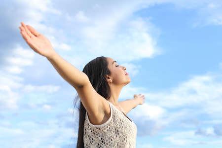 Portret van een mooie Arabische vrouw inademen van frisse lucht met opgeheven armen met een bewolkte blauwe hemel op de achtergrond