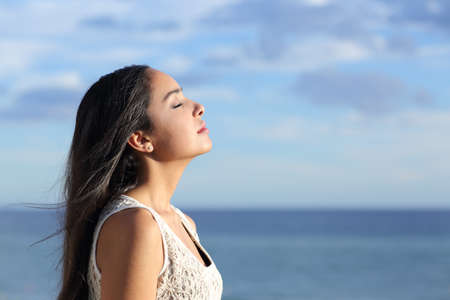 Profile of a beautiful arab woman breathing fresh air in the beach with a cloudy blue sky in the background photo