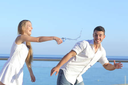 joking: Woman throwing water to her boyfriend with the sky in the background