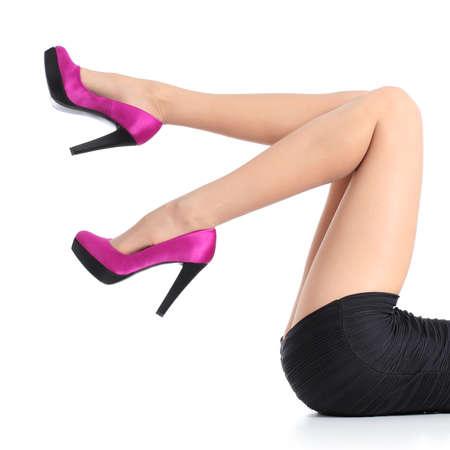 Piernas hermosas con los zapatos de tacón alto fucsia aislado en un fondo blanco