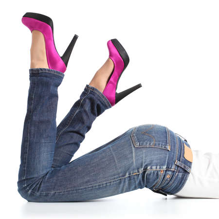 Beautiful woman legs with jeans and fuchsia high heels lying down isolated on a white background