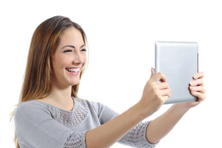 Beautiful woman laughing watching a digital tablet isolated on a white background photo
