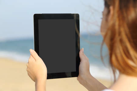Close up of a woman showing a big blank tablet screen on the beach with the sea in the background              photo