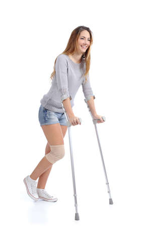 Beautiful woman smiling and hobbling with crutches isolated on a white background