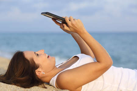 Side view of a teenager girl laughing and browsing her tablet pc lying on the sand of the beach photo