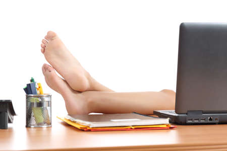 resting: Woman resting at work with the feet over the office table isolated on a white background