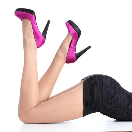 Mooie vrouw benen met fuchsia hoge hakken liggend op een witte achtergrond geà ¯ soleerde Stockfoto