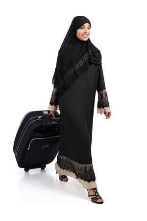 Arab woman walking carrying a suitcase isolated on a white background              Stock Photo