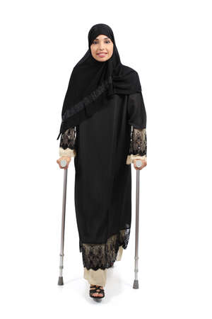 Arab woman walking with crutches isolated on a white background                photo