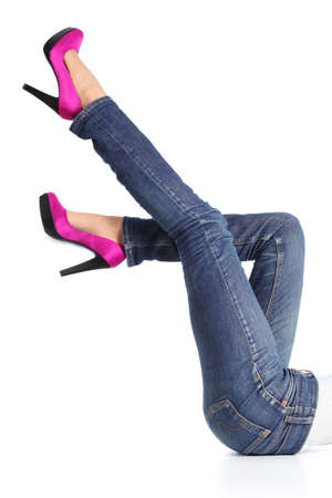 Woman legs with jeans and fuchsia high heels pointing up isolated on a white background              photo