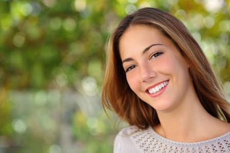 美しい女性の屋外の緑の背景を持つ完璧な白い笑顔で顔射 写真素材
