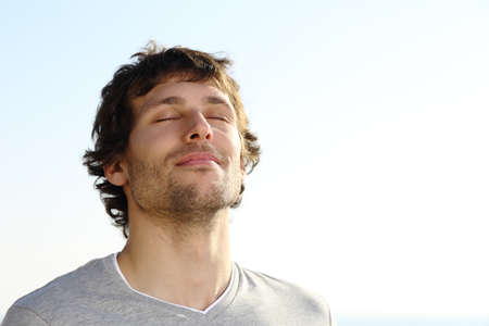 fresh air: Uomo attraente respirare all'aperto con il cielo sullo sfondo