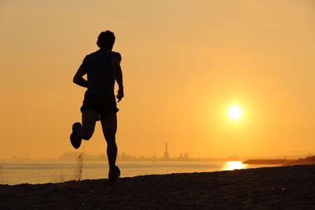 バック グラウンドで水平線と夕日、ビーチで走っている人のバックライト 写真素材