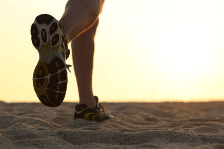 feet in sand: Legs and shoes of a man running at sunset with the horizon in the background