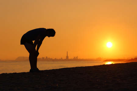 tired: Silhouette of an tired sportsman at sunset with a city in the background