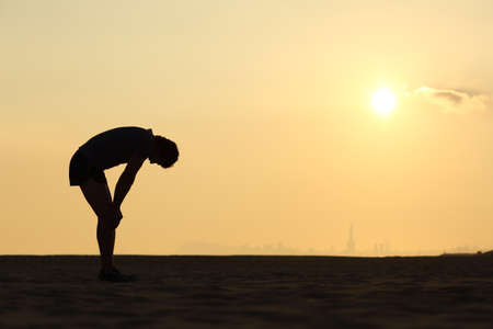 exhausting: Silhouette of an exhausted sportsman at sunset with the horizon in the background