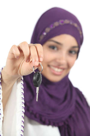 Arab woman holding and showing a car key isolated on a white background photo