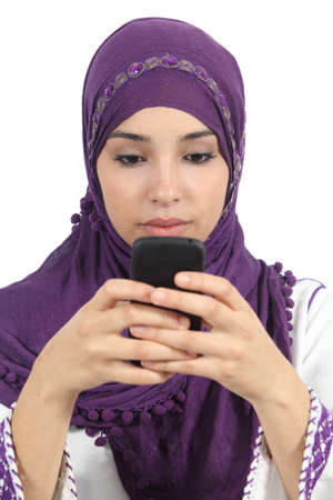 Arab woman writing a message addicted to the smart phone isolated in a white background               photo