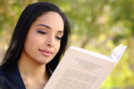 Close up of a beautiful woman reading a book in a park with a green unfocused background photo