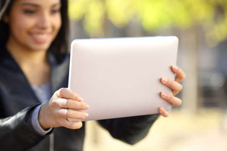 Close up of a woman holding and watching a digital tablet in a park photo