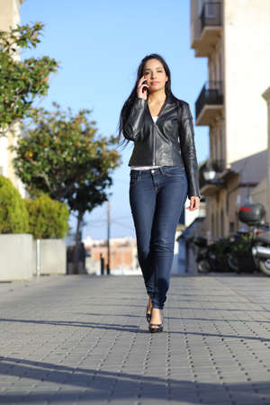 Front view of a fashion woman walking on the street talking on the mobile phone  photo