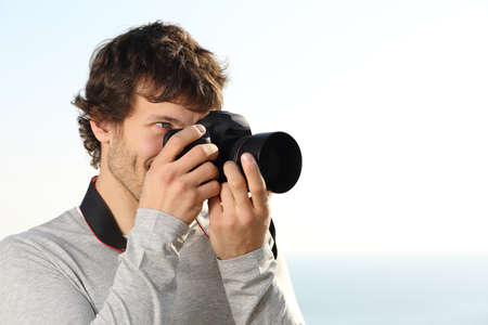 taking photograph: Attractive photograph photographing with a slr camera outdoor with the sky in the background