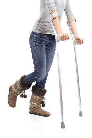 hobble: Close up of a casual woman walking with crutches isolated on a white background                 Stock Photo