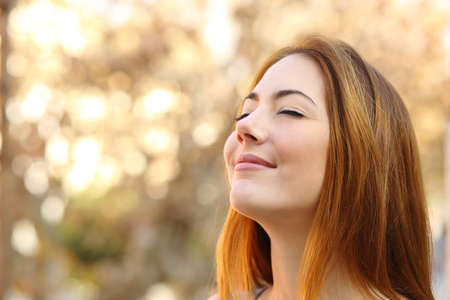 Portrait of a beautiful woman doing breath exercises with an autumn unfocused background photo