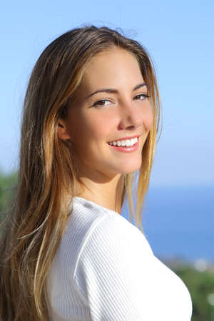 Portrait of a beautiful woman with a white perfect smile outdoor              Фото со стока