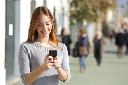 Portrait of a beautiful casual woman in the street browsing a smart phone photo