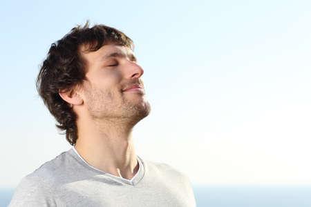 Primer plano de un hombre haciendo la respiración ejercicios al aire libre con el cielo en el fondo
