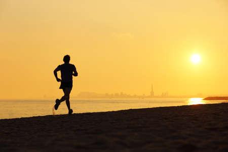 salud y deporte: Silueta del basculador corriendo en la playa al atardecer con el horizonte en el fondo
