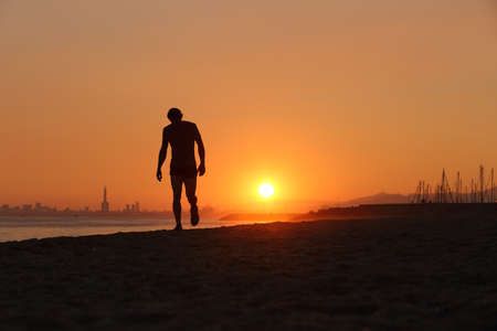 tired man: Jogger silhouette walking exhausted after a hard training at sunset Stock Photo