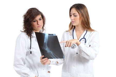 traumatology: Two female doctors watching a radiography isolated on a white background