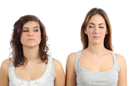 desconfianza: Dos muchachas que miran el uno al otro enojado aislado en un fondo blanco