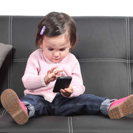 Cute baby browsing in a smartphone sitting on a black couch at home photo