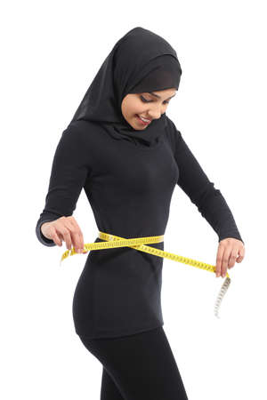 saudi: Arab woman measuring waist with a measure tape isolate don a white background           Stock Photo