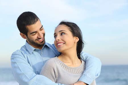 Arabische casual paar knuffelen blij met liefde op het strand met de horizon en de zee op de achtergrond Stockfoto