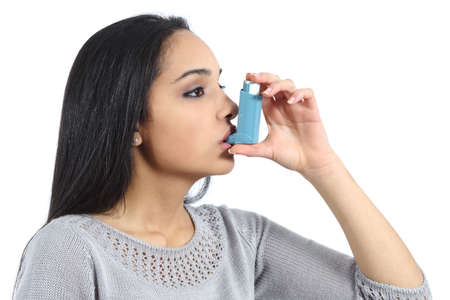 inhale: Asthmatic arab woman breathing from a inhaler isolated on a white background