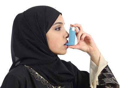 inhaler: Saudi arabian asthmatic woman breathing from an asthma inhaler isolated on a white background