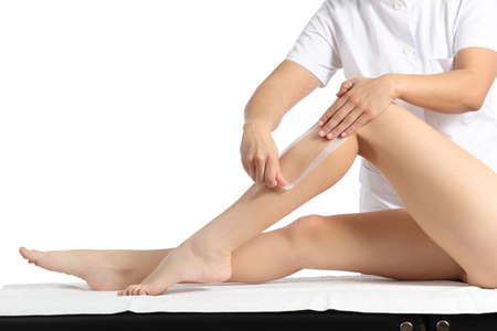 depilaciones: Esteticista depilaci�n una hermosa mujer de piernas suaves con una tira de cera aisladas sobre un fondo blanco
