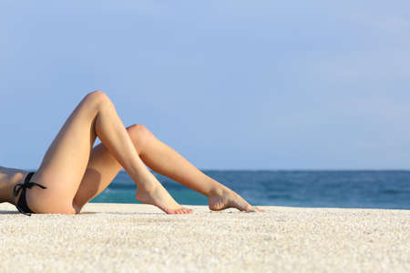 Profile of a beautiful woman legs resting on the beach sunbathing with the horizon in the background            Stock Photo