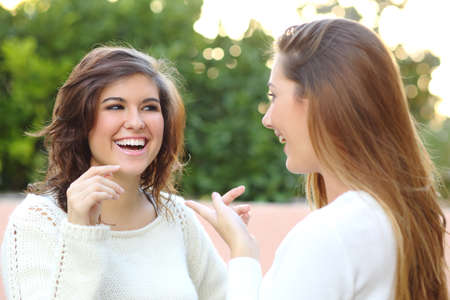 Two young women talking happy outdoor photo