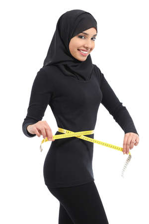 Beautiful arab saudi fitness woman measuring her waist with a tape measure and looking at camera isolated on a white background               Stock Photo